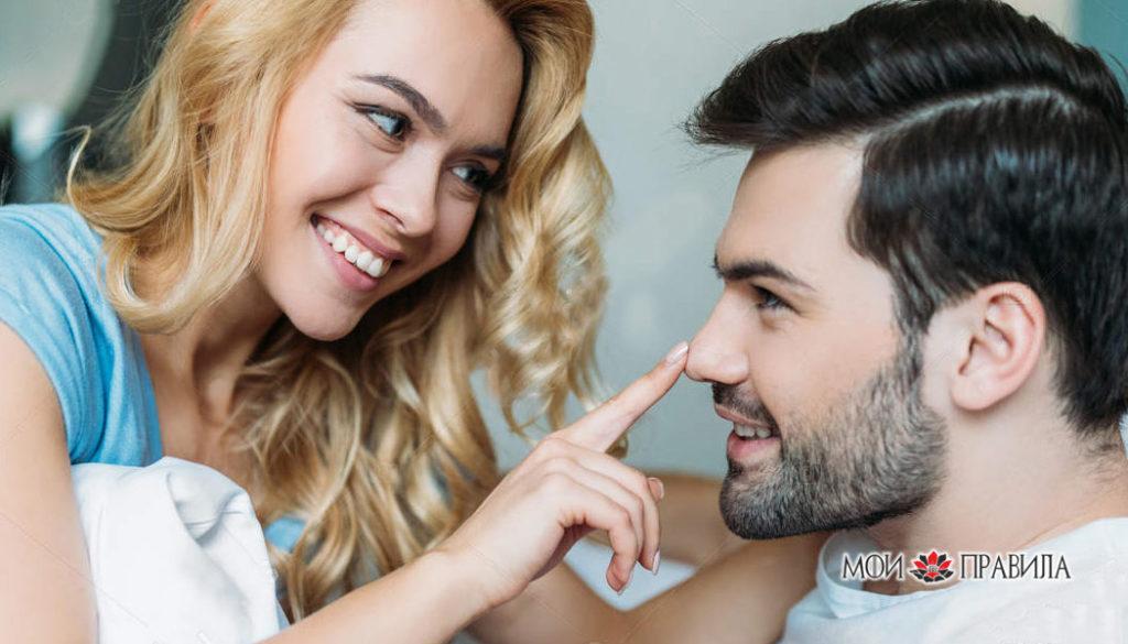 Улыбающаяся девушка трогает парня за нос в постели