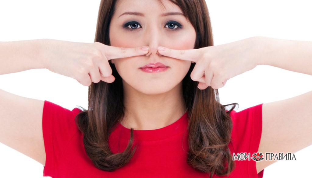 Милая молодая женщина держит нос пальцами.